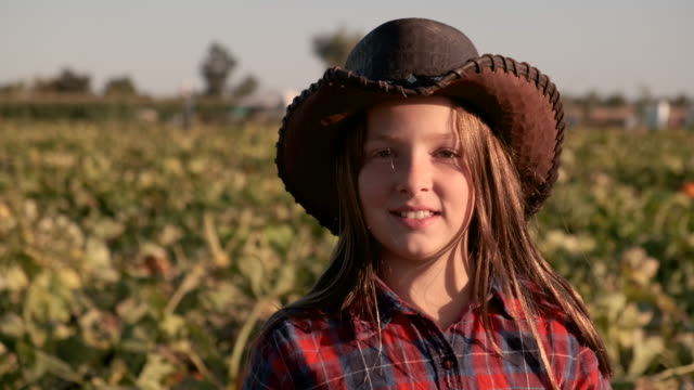 smiling ten years old american farm girl looking at the camera wearing a cowboy hat - rancher stock videos & royalty-free footage