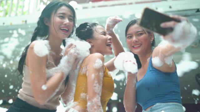 lächelnd drei junge frau, die selfie, während genießen in blasen auf der party - soap sud stock-videos und b-roll-filmmaterial