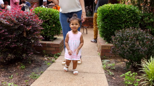 ms ts smiling toddler girl walking on pathway with mother during outdoor party with family and friends - 赤ちゃんの靴点の映像素材/bロール