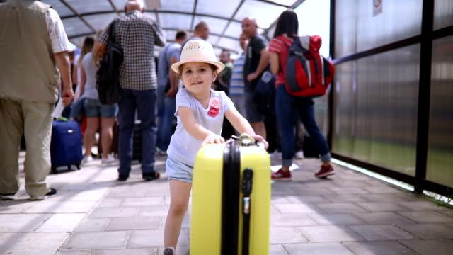 Sourire tout-petit poussant son coffre sur un aéroport