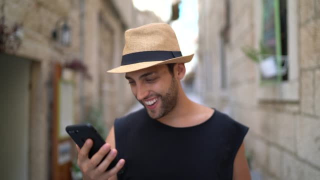 smiling tourist using mobile phone on the street - caucasian ethnicity stock videos & royalty-free footage