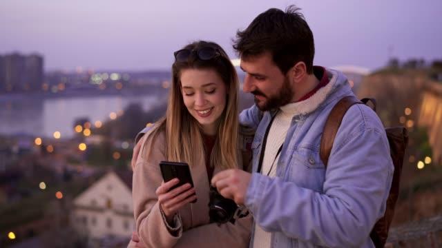 turisti sorridenti che usano il cellulare - tourist video stock e b–roll