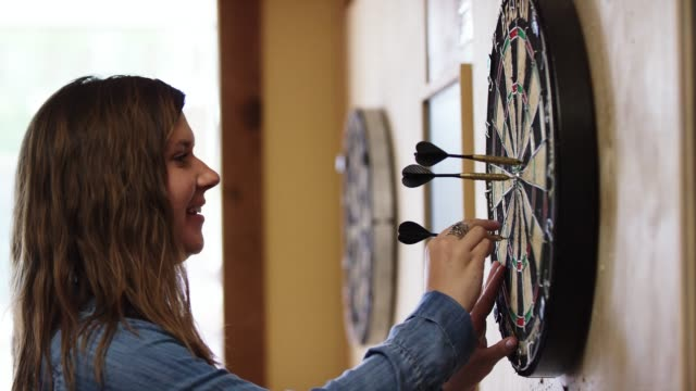 a smiling twenty-something caucasian woman pulls three darts out of a dartboard at a pub - dart board stock videos & royalty-free footage