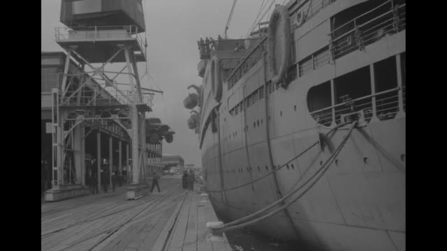 vídeos de stock e filmes b-roll de smiling us soldier in cap with bow of ship behind him / vs crane removing a jeep from the ship and lowering it to a dock / soldiers at dock with a... - baixar