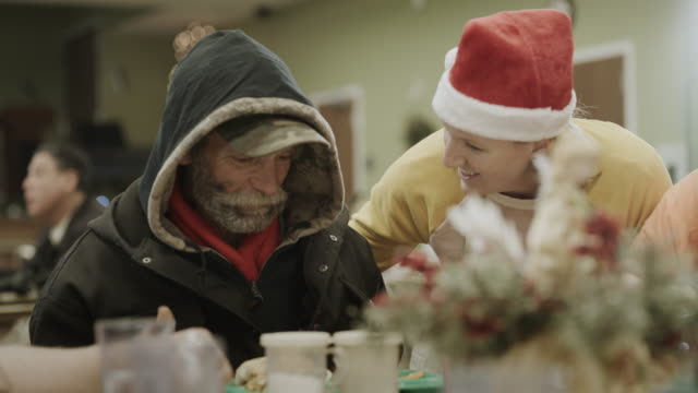 smiling volunteer wearing santa hat talking with man eating meal in homeless shelter / provo, utah, united states - canteen stock videos & royalty-free footage