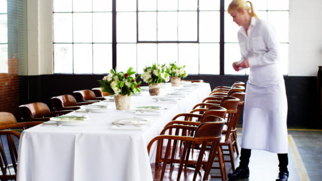 ms smiling waitress setting banquet table for dinner party in loft - banquet stock videos & royalty-free footage