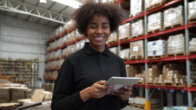 vídeos de stock e filmes b-roll de smiling warehouse worker holding digital tablet - transporte de mercadoria