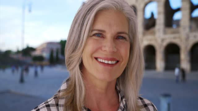 stockvideo's en b-roll-footage met smiling white female senior enjoys herself in front of roman colosseum - monument