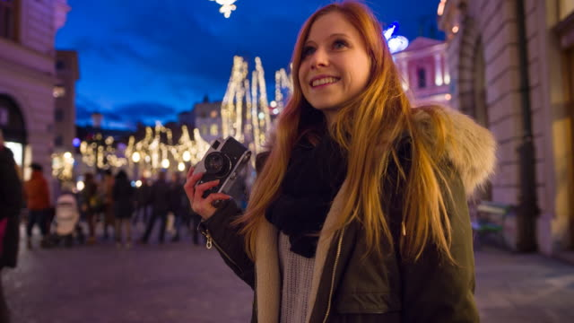 vídeos de stock e filmes b-roll de smiling woman admiring festive christmas decorations in the city - brightly lit