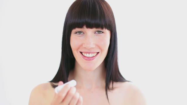 smiling woman applying lip balm on her lips - applying stock videos & royalty-free footage