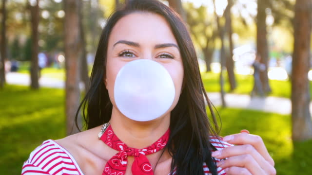 Smiling woman chewing gum and blowing bubble