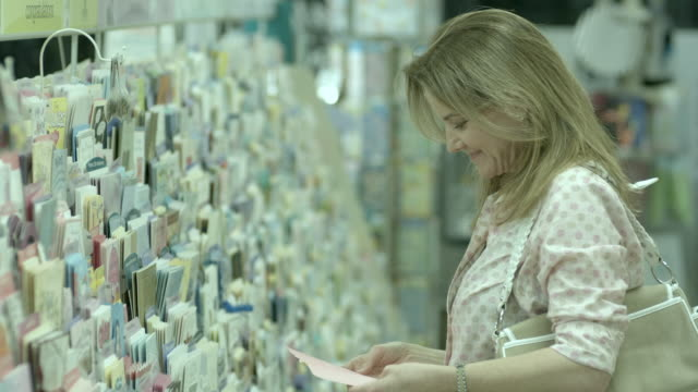 MS, SELECTIVE FOCUS, Smiling woman choosing greeting card in pharmacy aisle, Scotch Plains, New Jersey, USA