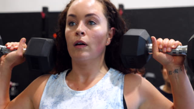 cu smiling woman doing dumbbell presses during fitness class in gym - effort stock videos & royalty-free footage