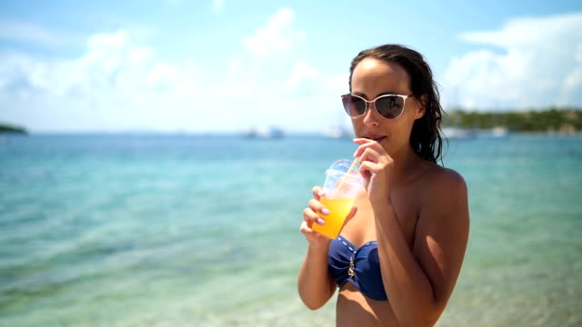 smiling woman drinking fresh juice by the sea - juice drink stock videos & royalty-free footage
