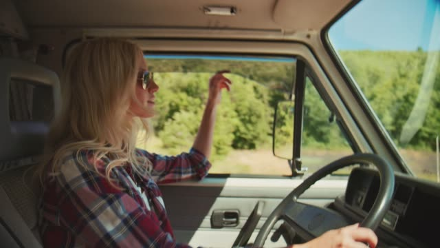 smiling woman driving van during summer vacation - blonde hair stock videos & royalty-free footage
