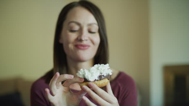 smiling woman eating chocolate donut with whipped cream / murray, utah, united states - whipped cream stock videos & royalty-free footage