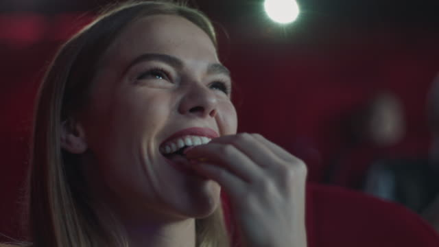 smiling woman eating popcorn in cinema - cinema stock videos & royalty-free footage