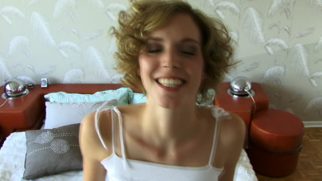 cu, smiling woman falling on bed - kopfkissen stock-videos und b-roll-filmmaterial