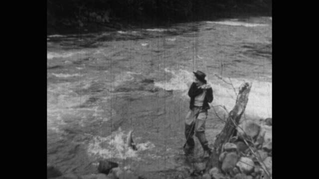 smiling woman fishing in river - trousers stock videos & royalty-free footage
