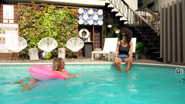 stockvideo's en b-roll-footage met ms smiling woman floating in inflatable ring in hotel pool while talking to wife sitting on pool deck - zwembadrand
