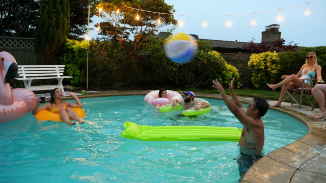 MS Smiling woman floating in inner tube while playing volleyball during pool party with friends on summer evening