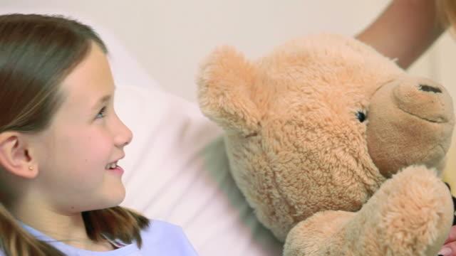 smiling woman giving a teddy bear to a smiling girl in a bed - kvinnlig läkare bildbanksvideor och videomaterial från bakom kulisserna
