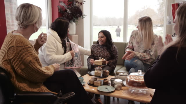 smiling woman giving gift to her friend in cafe - 30 39 years stock videos & royalty-free footage
