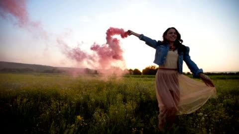 leende kvinna ha kul med färgad rök - fackla bildbanksvideor och videomaterial från bakom kulisserna