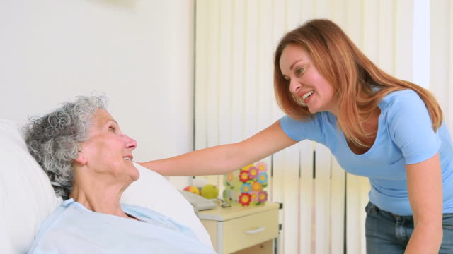Smiling woman holding the hand of a patient in a room