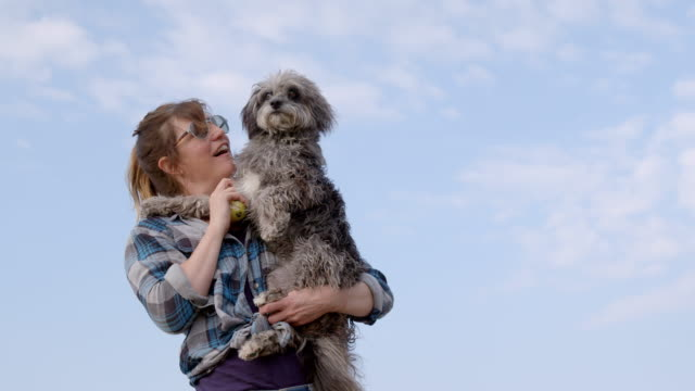 SLO MO smiling woman hugging Terrier on beach
