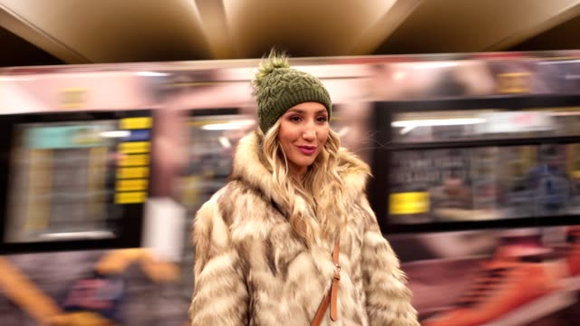 地下鉄で毛皮のコートでの笑顔の女性 - 毛皮のコート点の映像素材/bロール