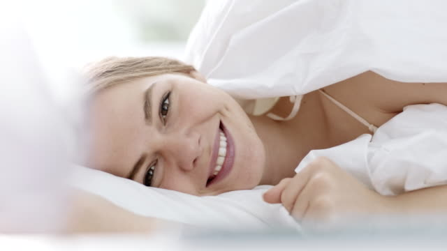 smiling woman in bed - duvet stock videos & royalty-free footage