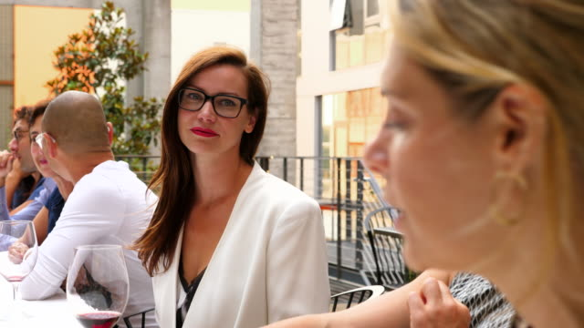 ms smiling woman in discussion with friend during dinner party on restaurant patio - 40 44 jahre stock-videos und b-roll-filmmaterial