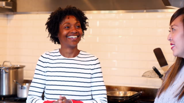 MS Smiling woman in discussion with friends before cooking class in commercial kitchen