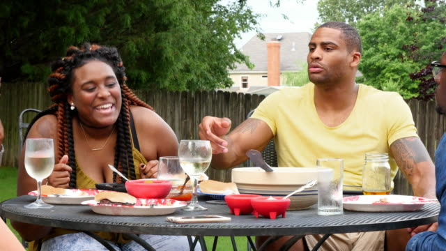 MS Smiling woman in discussion with friends during backyard party