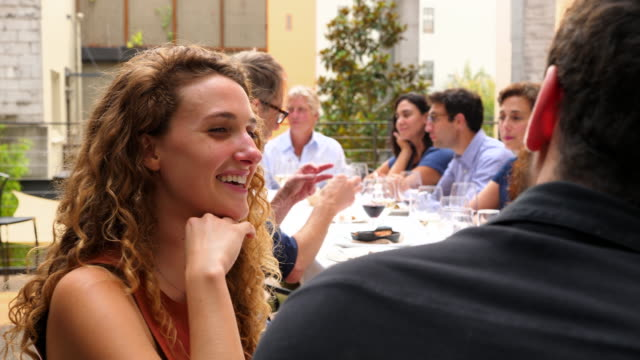 ms smiling woman in discussion with friends during dinner party on patio on summer evening - dinner party stock videos & royalty-free footage