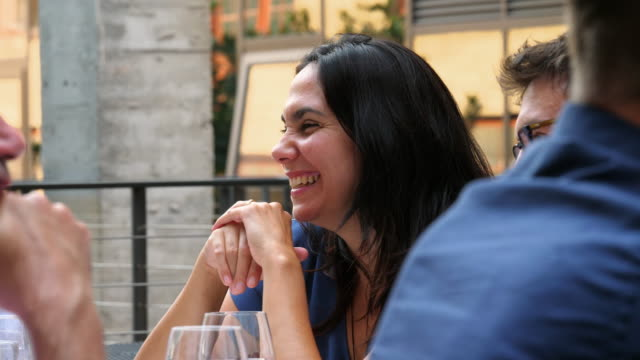 rf smiling woman in discussion with friends during dinner party on restaurant patio - dinner party stock videos & royalty-free footage