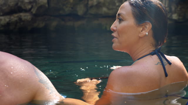 ms smiling woman in discussion with husband while relaxing in cenote during vacation - real wife sharing stock-videos und b-roll-filmmaterial