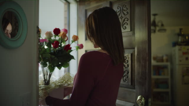 smiling woman in doorway receiving delivery of bouquet of flowers / murray, utah, united states - giving stock videos & royalty-free footage