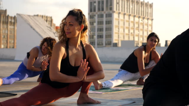 ms smiling woman in extended leg squat pose during yoga class on rooftop on rooftop - trousers stock videos & royalty-free footage
