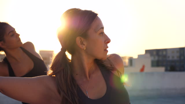 ms smiling woman in rooftop yoga class with friends at sunset - stretching stock videos & royalty-free footage