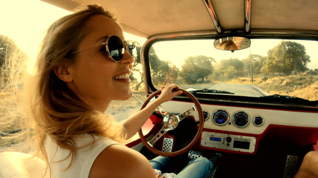 smiling woman in sunglasses with blond hair drives a car - sun roof stock videos & royalty-free footage