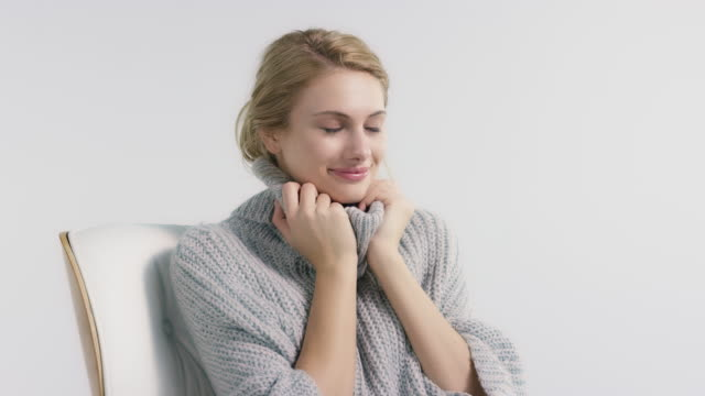 smiling woman in sweater against white background - morbidezza video stock e b–roll