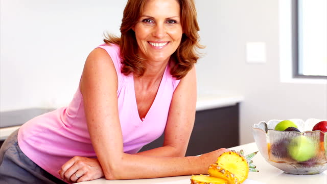 smiling woman leaning on kitchen counter - femininity stock videos & royalty-free footage