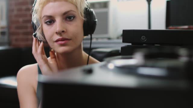 vídeos y material grabado en eventos de stock de mujer sonriente escuchando música en casa - auriculares equipo de música