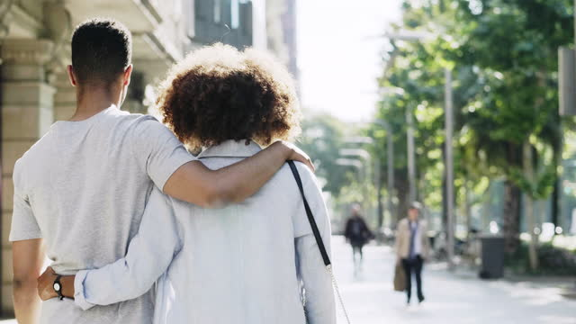 smiling woman looking back while walking with boyfriend in the city - arm around stock videos & royalty-free footage