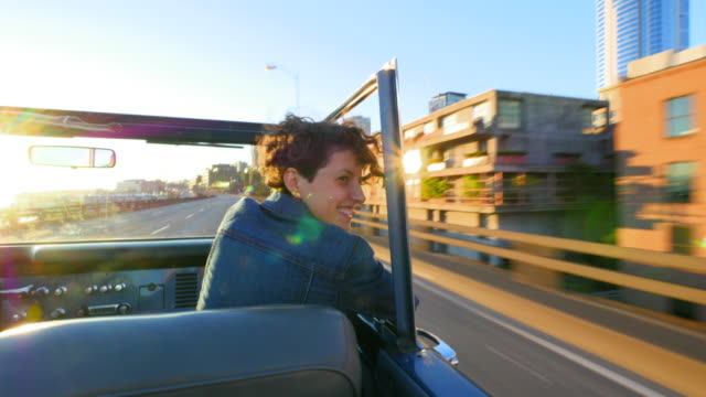 MS Smiling woman looking out of passenger window of convertible laughing with boyfriend while driving along city overpass