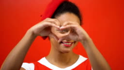 Smiling woman making heart with hands, kindness, charity work, red background