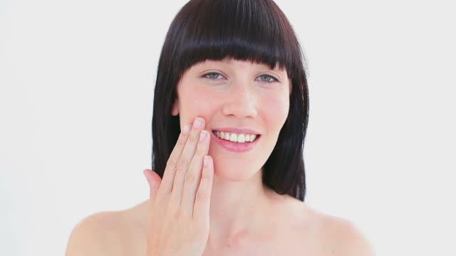 Smiling woman massaging her cheek