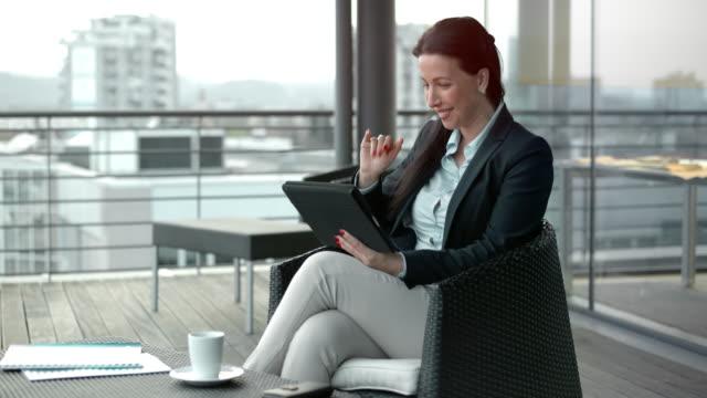vídeos y material grabado en eventos de stock de mujer sonriente en una llamada de video sentado en el salón terraza con vistas a la ciudad - conferencia telefonica